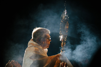 Photo of a priest holding up a monstrance containing Jesus in the Eucharist.