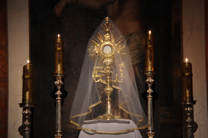 A veiled monstrance with the Blessed Sacrament exposed.