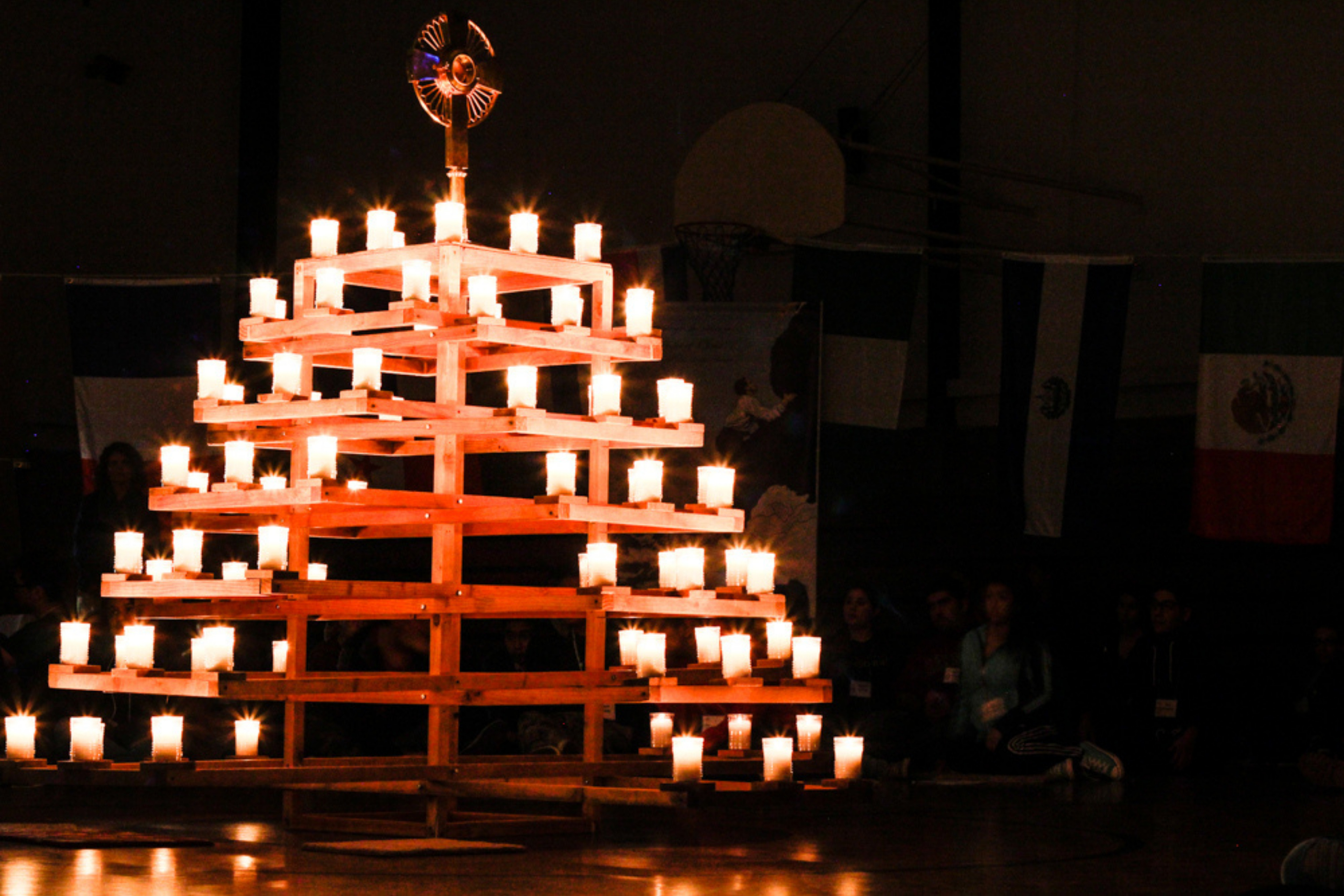 """The Eucharist exposed atop a """"Burning Bush"""" of lit candles."""