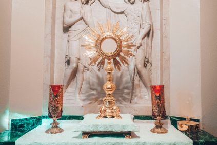 A photo of the Blessed Sacrament exposed in a monstrance, with lit candles either side.