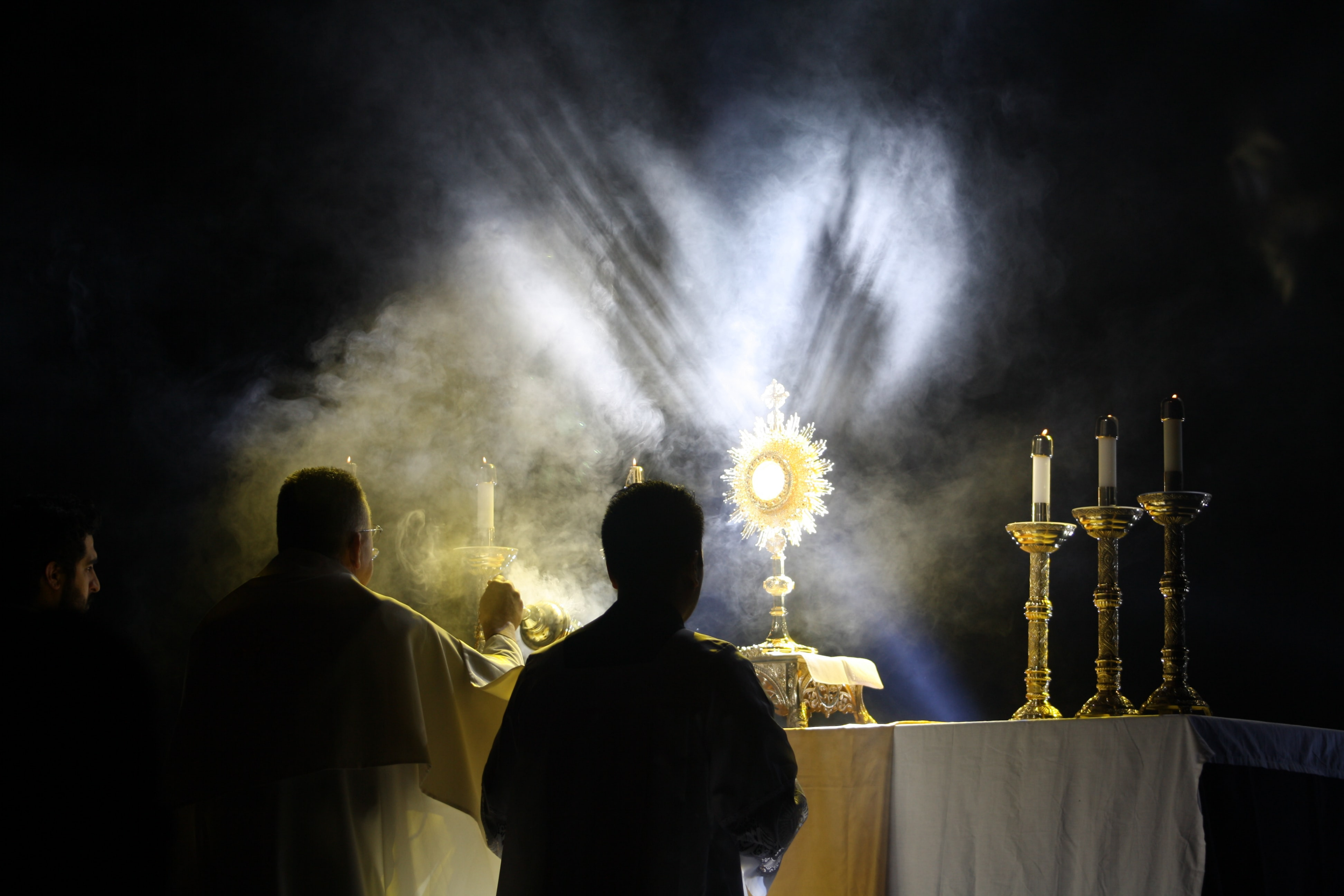 Two men praying before Jesus in the Blessed Sacrament.
