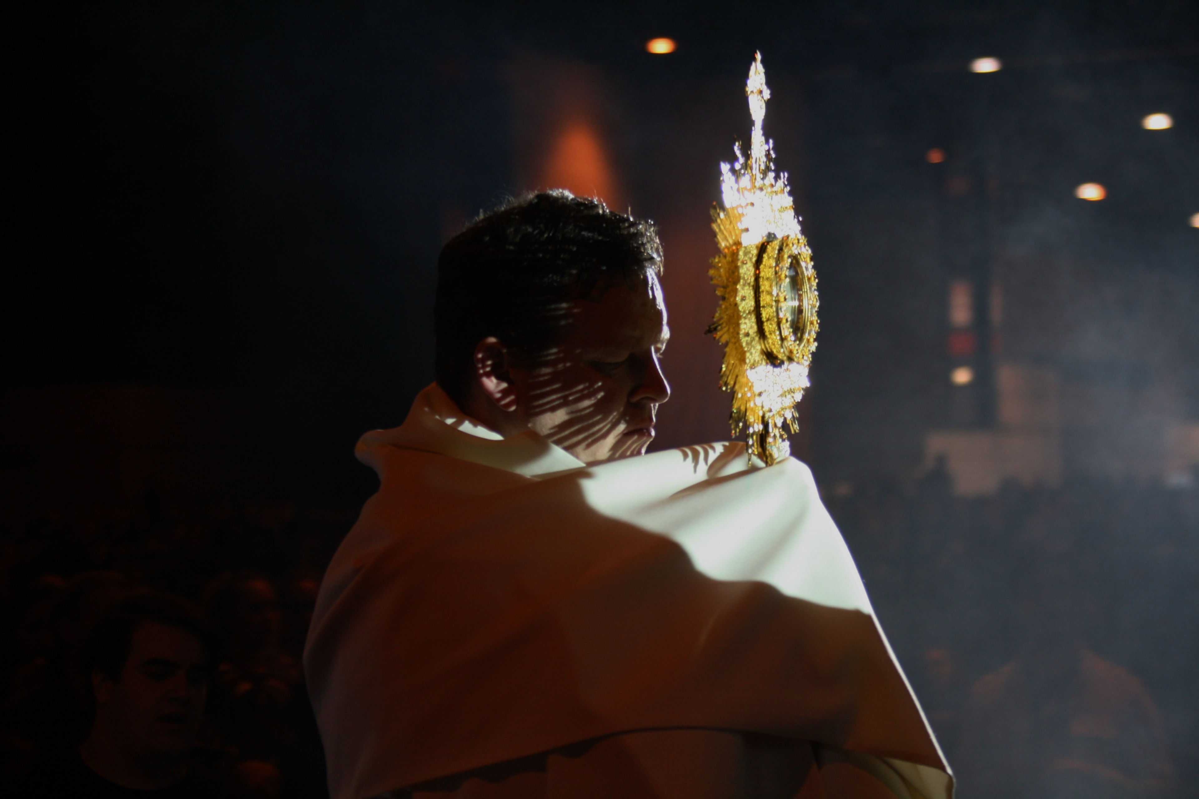 A priest raises the Blessed Sacrament for Benediction.
